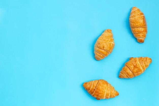 Lekkere croissants op blauwe achtergrond.
