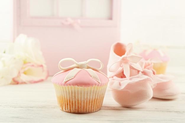 Lekkere cupcake met boog en baby schoenen decoratieve kinderwagen op kleur achtergrond