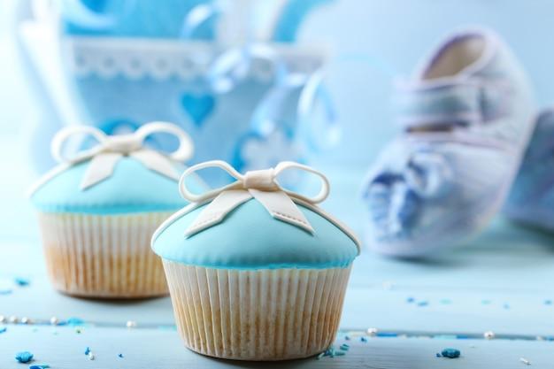Lekkere cupcake met strik en baby schoenen op een houten achtergrond kleur