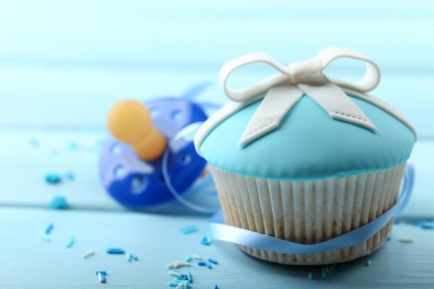 Lekkere cupcake met strik en babyfopspeen op een houten achtergrond kleur