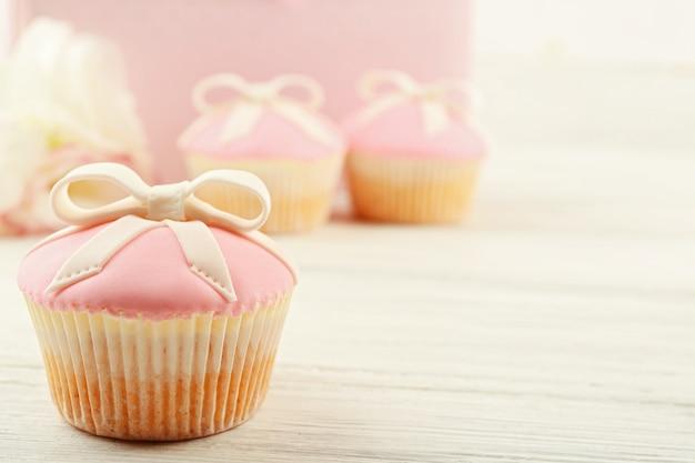 Lekkere cupcake met strik en babyschoentjes, decoratieve kinderwagen op kleuroppervlak