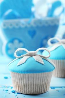 Lekkere cupcake met strik en babyschoentjes op een houten kleurtafel