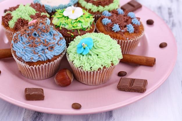 Lekkere cupcakes met botercrème, op plaat, op grijze houten tafel