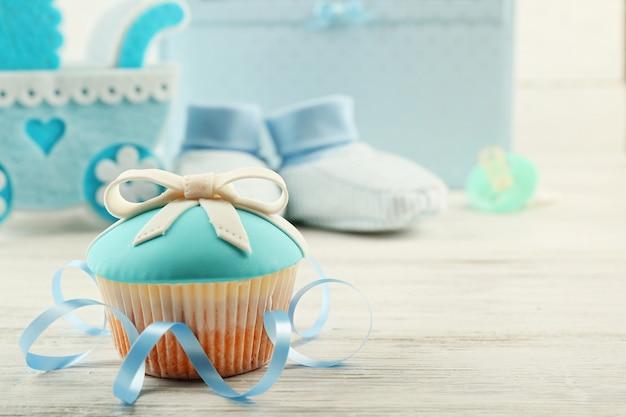 Lekkere cupcakes met strik en babyschoentjes, decoratieve kinderwagen en fotoalbum op gekleurde achtergrond