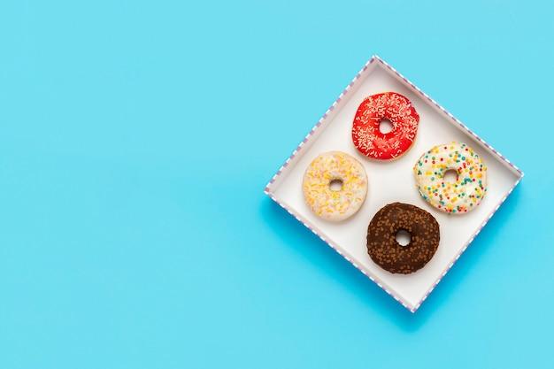 Lekkere donuts in een doos op een blauwe achtergrond. concept van snoep, bakkerij, gebak, coffeeshop. banier. plat lag, bovenaanzicht.