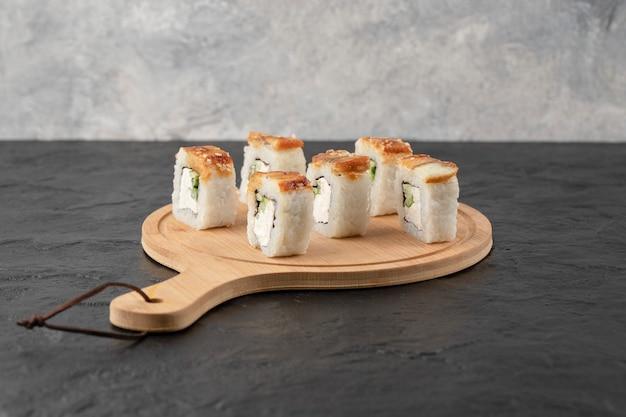 Lekkere drakensushibroodjes met paling op een houten bord