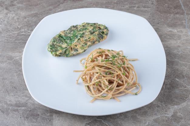 Lekkere eierkotelet met groenen en spaghetti op witte plaat.