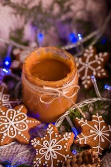 Lekkere en geurige chocoladeschilferkoekjes worden verpletterd met poedersuiker, met veelkleurige lichten op tafel. vrolijk kerstfeest