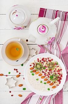 Lekkere en gezonde havermoutpap met kiwi, granaatappel en zaden. gezond ontbijt. fitness eten. goede voeding. bovenaanzicht