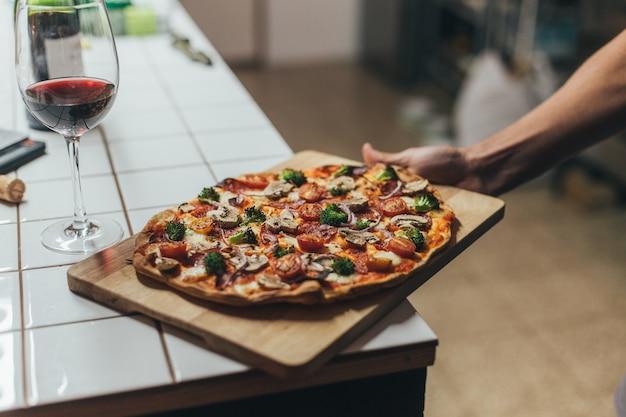 Lekkere en heerlijke huisgemaakte volkoren biologische en natuurlijke pizza met groenten en kaas voor een romantisch diner met wijn