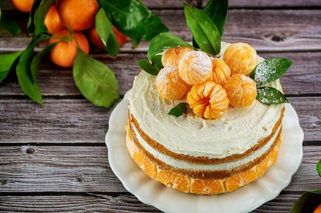 Lekkere feestelijke cake met gepelde mandarijnen en groene bladeren.