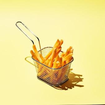 Lekkere frietjes in metalen draadmand op gele tafel in zonlicht.