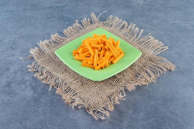 Lekkere frietjes op een bord op textuur, op de marmeren achtergrond.