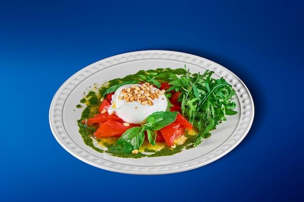 Lekkere, frisse salade met mozzarella burrata, rucola, cherrytomaatjes en basilicum op witte plaat. zachte italiaanse kaasburrata. italiaanse keuken. detailopname