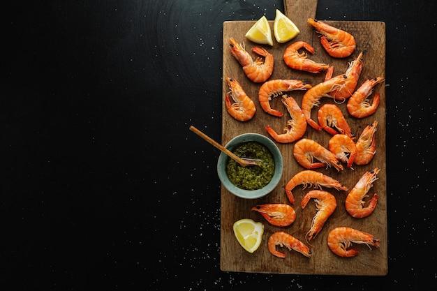 Lekkere garnalen met kruiden en saus aan boord op een donkere ondergrond