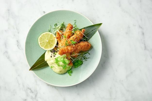 Lekkere garnalenfrietjes, gepaneerd met witte saus, groene tobiko kaviaar en limoen gearchiveerd in een groene plaat op een marmeren tafel. garnalen in aziatische stijl. restaurant zeevruchten
