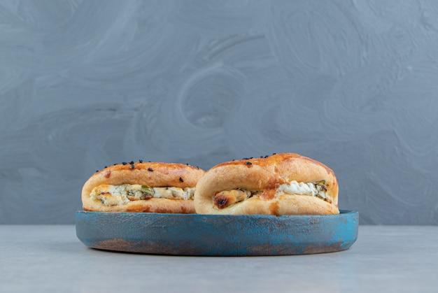 Lekkere gebakjes gevuld met kaas op blauw bord.