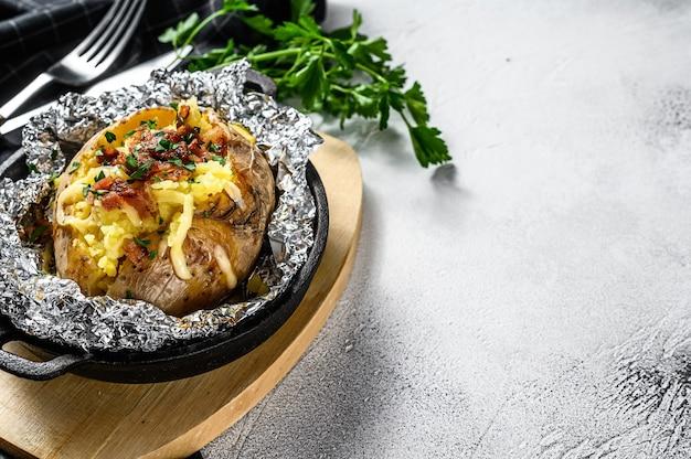 Lekkere gebakken aardappel gegarneerd met cheddarkaas en bieslook. witte achtergrond