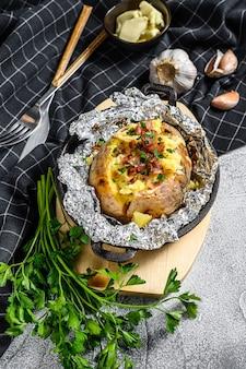 Lekkere gebakken aardappel gegarneerd met cheddarkaas en bieslook