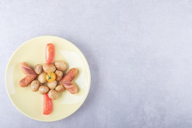 Lekkere gebakken aardappelen op gele plaat.