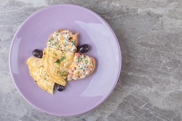 Lekkere gebakken eieren op paarse plaat.