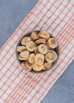 Lekkere gedroogde vruchten in kom op de handdoek, op de marmeren achtergrond.