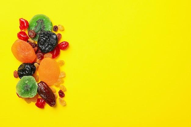 Lekkere gedroogde vruchten op gele achtergrond, ruimte voor tekst