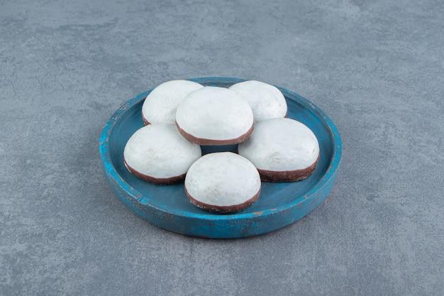 Lekkere geglazuurde koekjes op blauw bord.