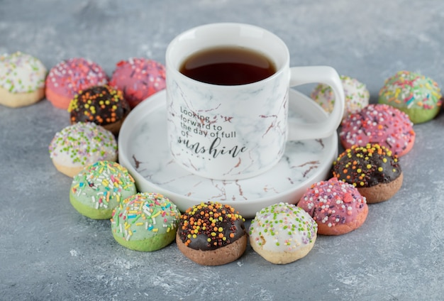 Lekkere geglazuurde koekjes rond kopje thee.