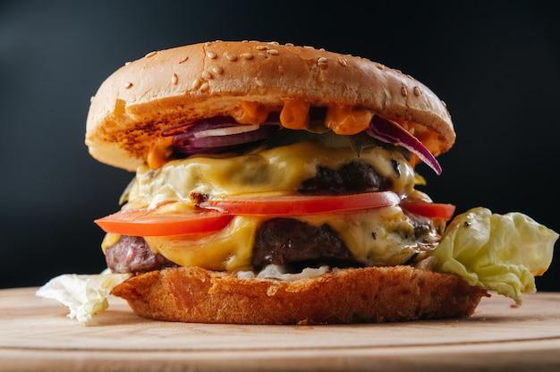 Lekkere gegrilde grote cheeseburger op een houten bord close-up premium foto