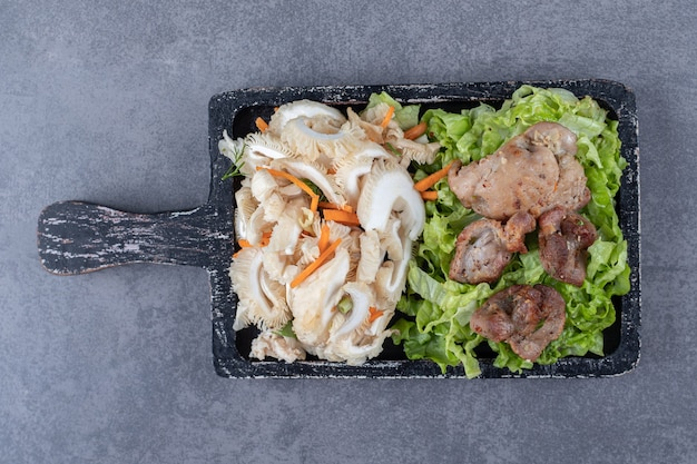 Lekkere gegrilde kebab en groentesalade op een houten bord.