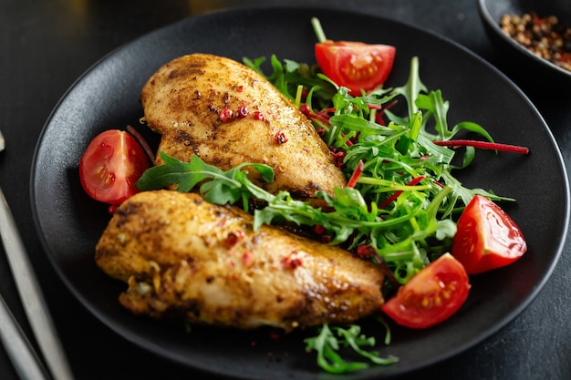 Lekkere gegrilde kipfilet met groenten en salade geserveerd op donkere tafel