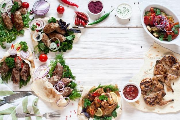 Lekkere gegrilde maaltijden frame op hout plat leggen. bovenaanzicht op assortiment hete bbq-vleessnacks, gratis