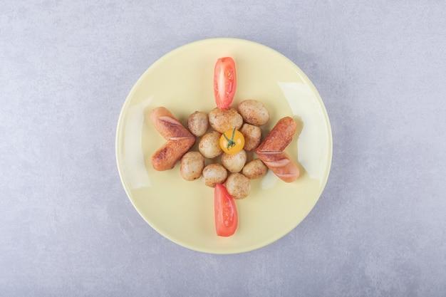 Lekkere gegrilde worstjes en aardappelen op gele plaat.