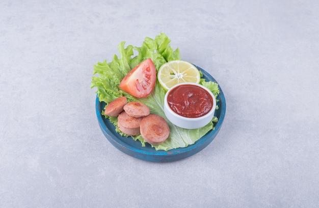 Lekkere gegrilde worstjes en ketchup op blauw bord.