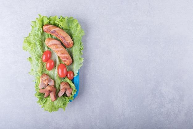 Lekkere gegrilde worstjes en tomaten op blauw bord.