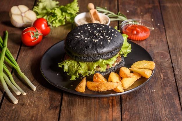 Lekkere gegrilde zelfgemaakte hamburger. heerlijke gegrilde hamburgers. ambachtelijke rundvleeshamburger en frieten op houten lijst