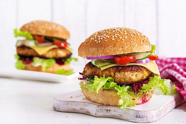 Lekkere gegrilde zelfgemaakte hamburger met hamburger kip, tomaat, kaas, komkommer, sla en rode biet. belegd broodje. lunch