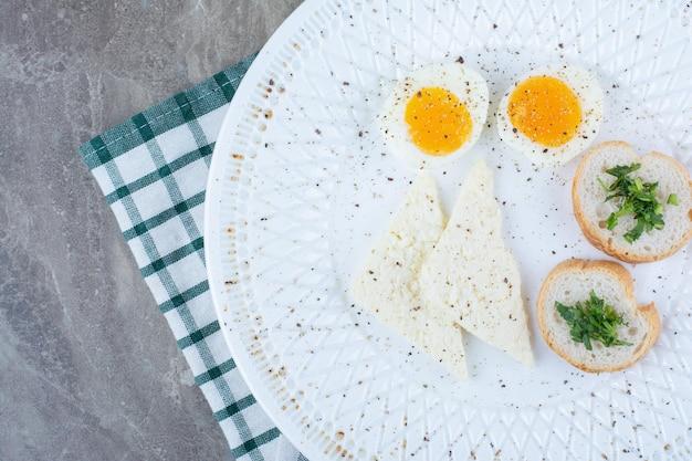 Lekkere gekookte eieren met kruiden en brood op tafellaken. hoge kwaliteit foto
