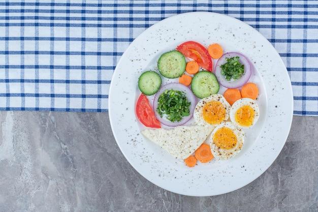Lekkere gekookte eieren met kruiden en groenten op tafellaken. hoge kwaliteit foto