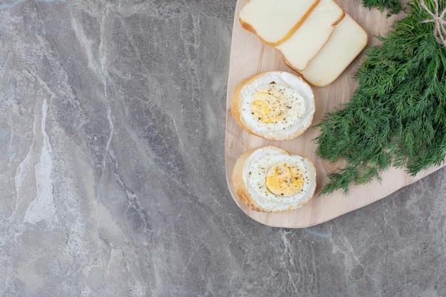 Lekkere gekookte eieren op wit brood met groenen op een houten bord. hoge kwaliteit foto
