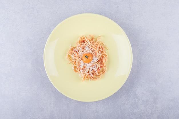 Lekkere gekookte spaghetti met tomaten op gele plaat.