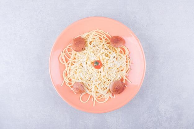 Lekkere gekookte spaghetti met worstjes op oranje plaat.