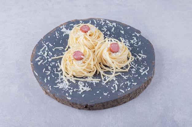 Lekkere gekookte spaghetti met worstjes op stuk hout.