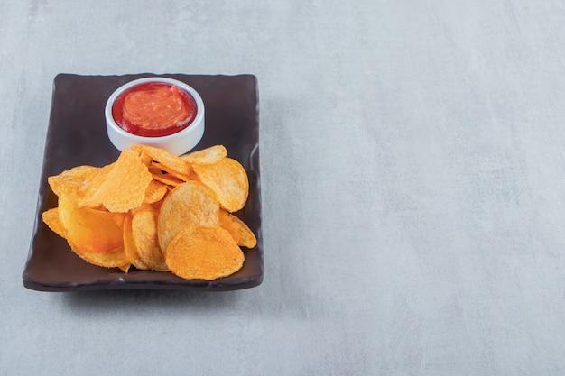Lekkere gekruide chips en ketchup op donkere plaat.