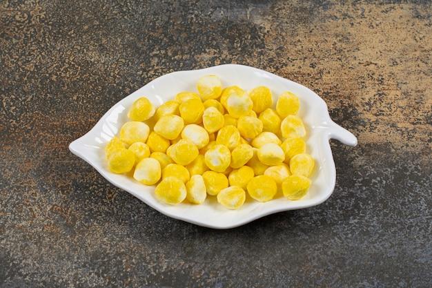 Lekkere gele snoepjes op bladvormige plaat.
