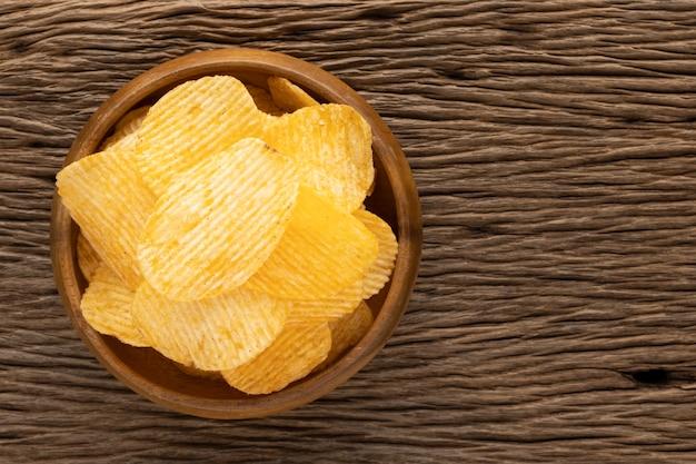 Lekkere geribbelde chips in houten kom op rustieke natuurlijke houtstructuur achtergrond, bovenaanzicht
