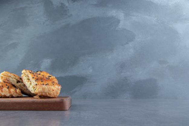 Lekkere gevulde gebakjes op een houten bord.
