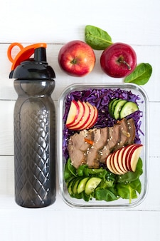 Lekkere gezonde lunch van groenten, gebakken kalkoen en een fles water. salade van rode kool, spinazie, appels, verse komkommers met dieet vlees in een glazen lunchbox op een witte houten oppervlak.