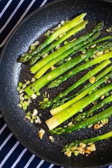 Lekkere groene asperges worden gebakken in een pan met knoflook, ernaast ligt een blauw gestreepte handdoek. close-up, bovenaanzicht.